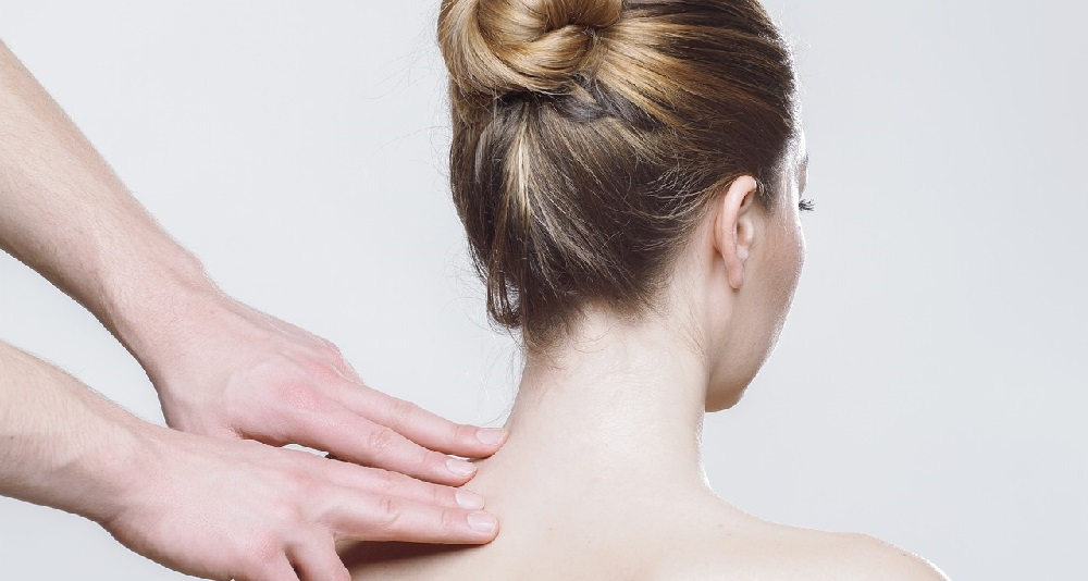 Two hands finger massaging neck of woman