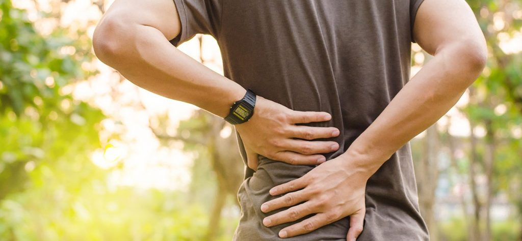 Man holding lower back on side with both hands from pain