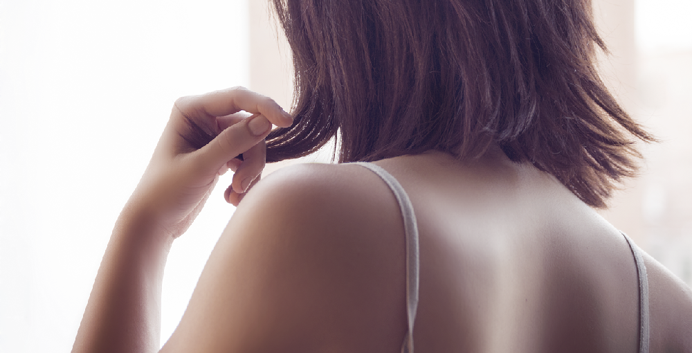 Back view of woman running hands through her hair