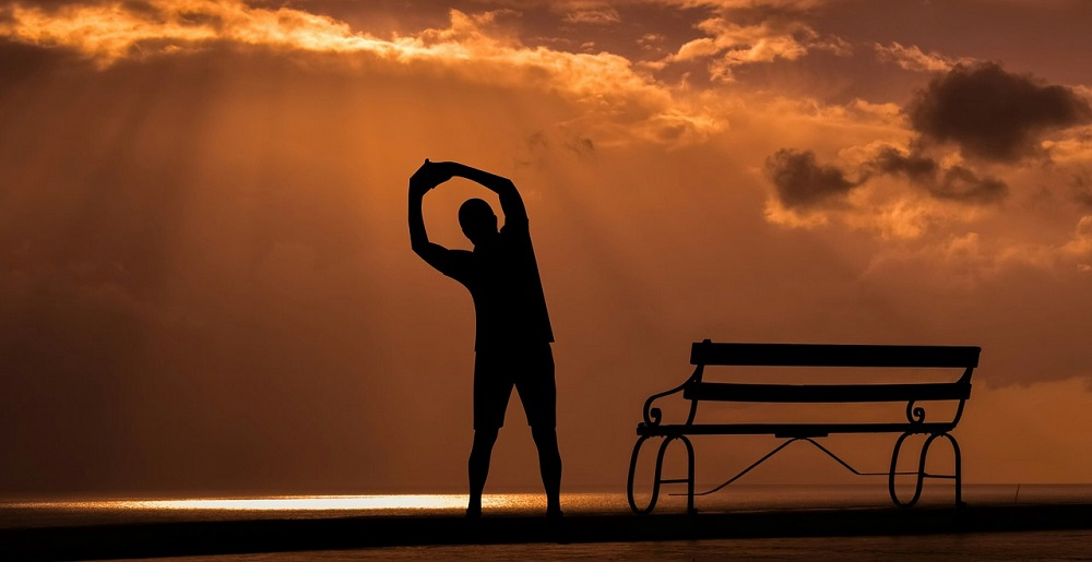 Silhouette of person doing side stretches under orange sky