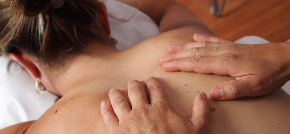 Woman getting massage with hands on upper back