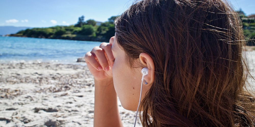 Girl meditating on beach with earbuds on beach