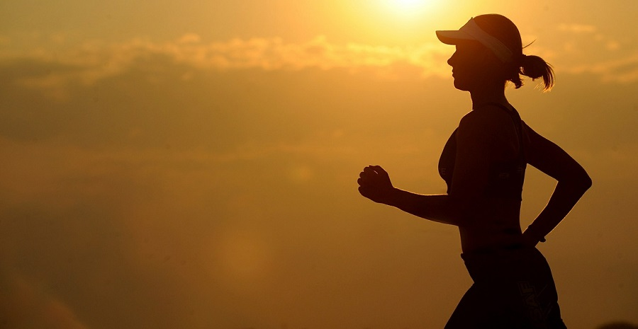 Silhouette of woman running with sunset