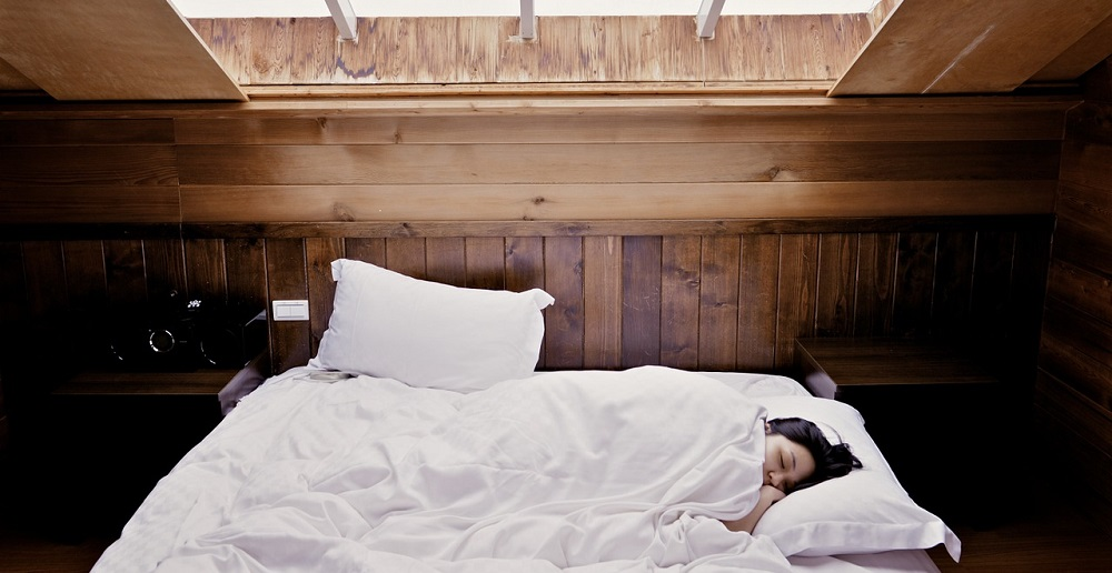 Woman sleeping in bed under covers