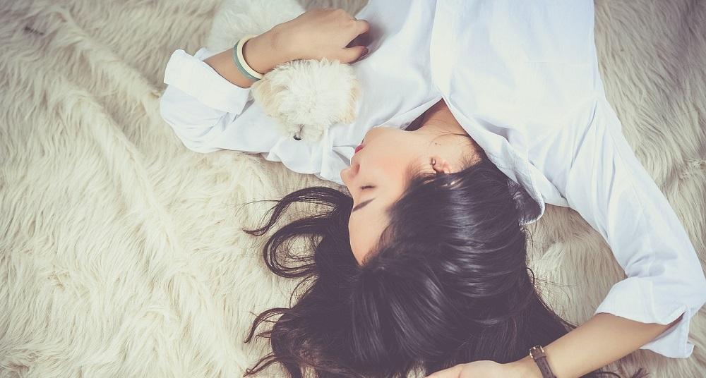 Woman sleeping with small dog