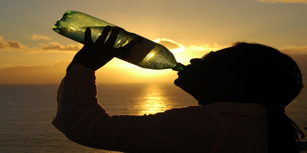 Silhouette of person drinking from water bottle