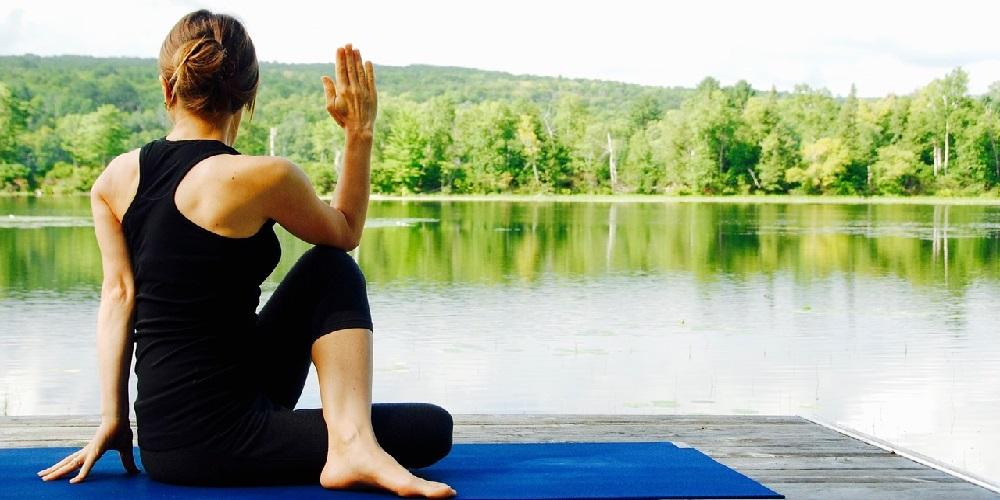 Woman twisting doing yoga on mat at a lake